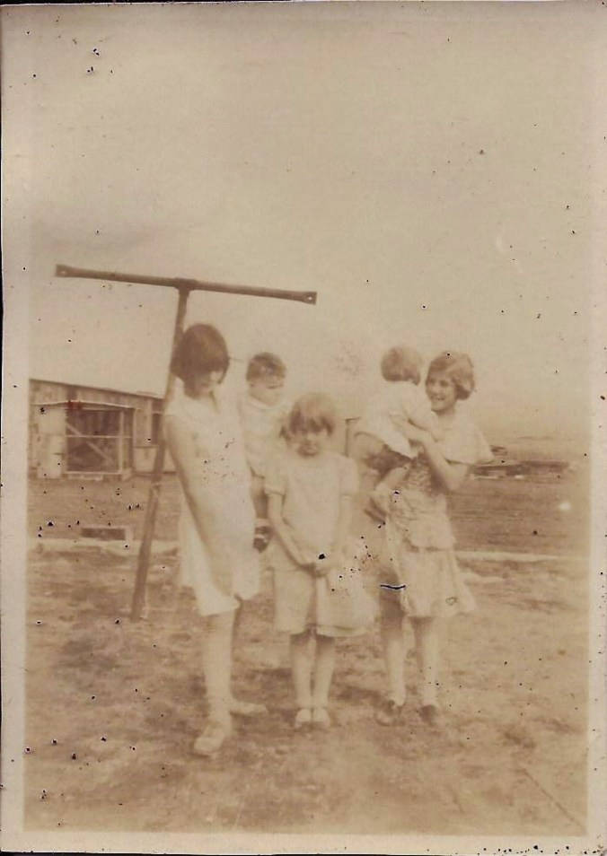 Here's Gail (center) with some cousins and her older sister. The wooden building in the background is the wash-house.
