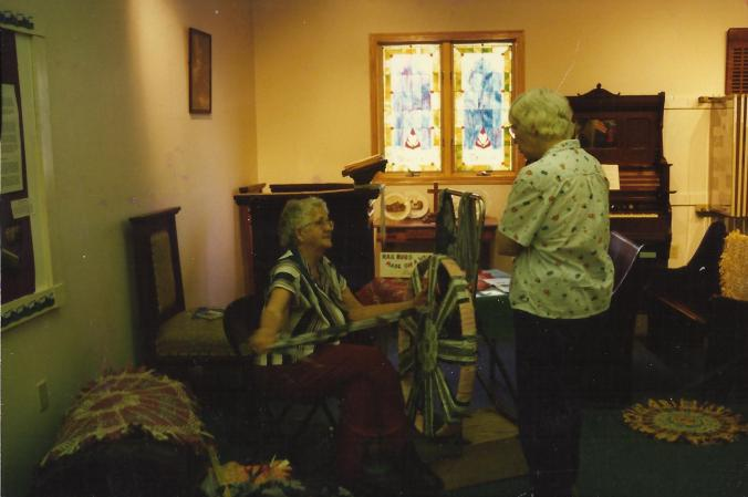 Gail Martin showing the technique for making round rag rugs on a wagon wheel rim. See the finished rugs on display around her.