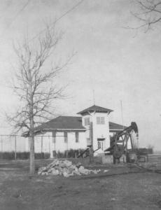 View of the Seeley School with an oil pump jack in front.
