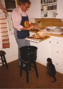 Dad is carving the turkey for Thanksgiving dinner. Lil Cat looks on hopefully.