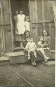 From our family album, a 1930s picture. My mother is the littlest girl standing in the doorway. The others are her cousins.  Teterville, Kansas