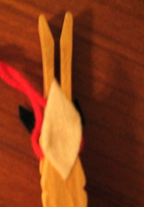 The reindeer's tail and the red yarn for hanging it on the tree.