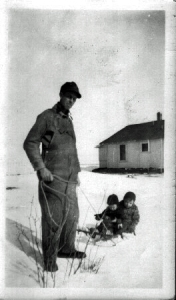 Clarence McGhee pulling toddlers on a sled. Kansas Flint Hills.